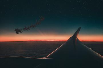 Slitta con Renne e babbo natale vista fuori dal finestrino di un aereo di linea al tramonto.