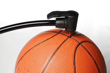 Air pump fills an orange basketball