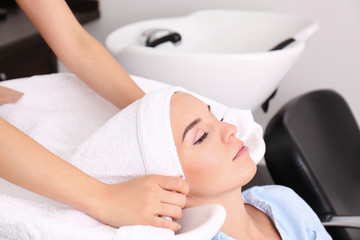 Hairdresser wrapping towel on customer's head