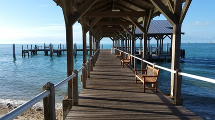 Covered Wood Pier Dock On The Ocean Water On The Horizon