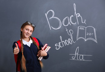 Girl with backpack and books standing near school blackboard