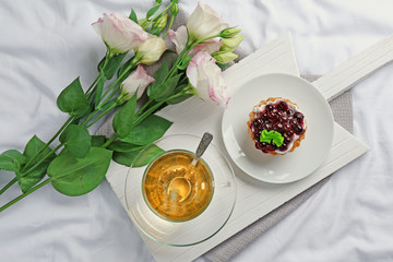 Romantic breakfast with cup of tea and cake on white bed