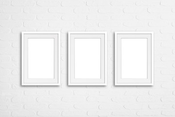 Three blank frames on white bricks textured wall, decoration mock up
