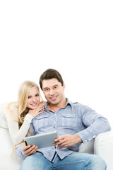 Smiling couple sitting on couch with laptop.