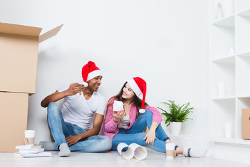 Couple in Santa hats in new house with packed moving.
