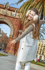 cheerful fashion-monger in Barcelona, Spain walking on parapet