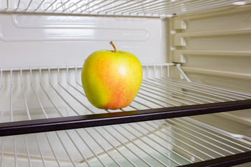 A yellow apple on a shelf in a refrigerator