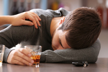 Drunk man with car key and alcoholic beverage in bar. Don't drink and drive concept