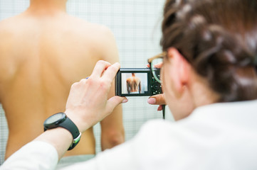 Close up Female Physiotherapist in her practice, makes photo shoot of the male pacient's back