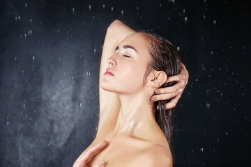 Beautiful young woman washing body in a shower