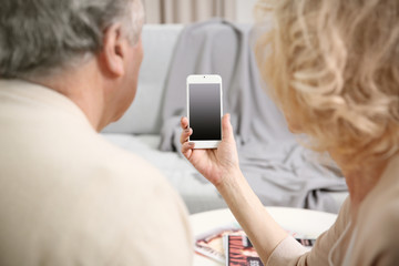 Senior couple making video call from mobile phone at home