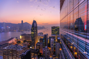 Spectacular aerial view of Victoria Harbor, skyscrapers and Hong Kong skyline at night. Skyline reflected in glass facade of a modern building.