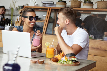 People, technology and leisure. Two friends having nice conversation, using laptop computer at modern cafeteria. Woman in sunglasses holding smoothie and laughing while talking to charismatic man
