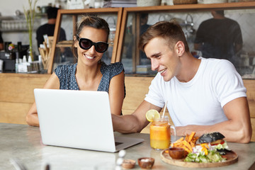 Handsome young man wearing white t-shirt showing something on laptop pc to his attractive female companion in stylish sunglasses during lunch at cafe, woman looking at screen with joyful smile