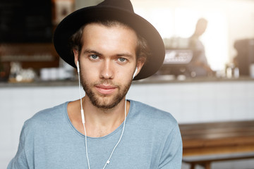 People and lifestyle concept. Portrait of smiling handsome young bearded man wearing stylish hat and t-shirt relaxing at cafe, listening to music on white earphones using some electronic device