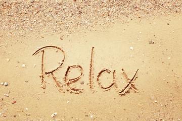 Word RELAX on beach sand
