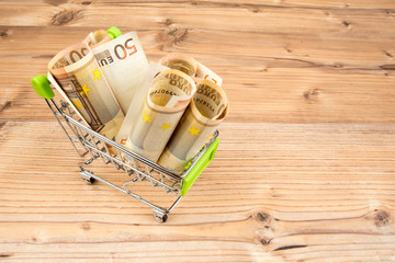 Self-service supermarket full shopping trolley with 50 euro banknotes. Shopping supermarket cart with green handle on wooden background. Shopping, money spending concept. Top, side view. Copy space.