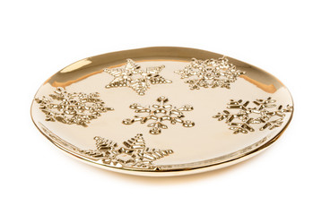 Luxurious gold plate decorated with winter ornaments – snowflakes.  Round gold plate, isolated on white background.  Winter, Christmas, New Year decoration. Side view.