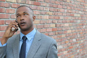 Portrait of bored businessman talking on cellphone against brick wall background