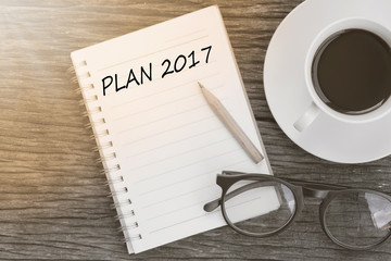 Plan 2017 On notebook with coffee cup, glasses and pencil on woo