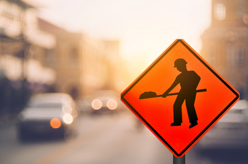 Construction warning sign on blur traffic road with colorful bokeh light abstract background.