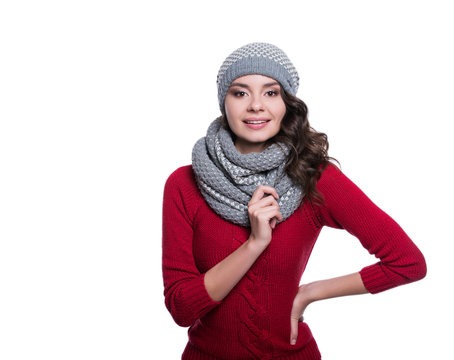Pretty cheerful sexy young woman wearing knitted sweater, scarf and hat. Isolated on white background. She is smiling. Winter clothes.