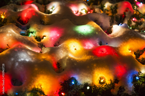 Christmas Lights Under The Snow Background Of Multicolored Spots Light Covered