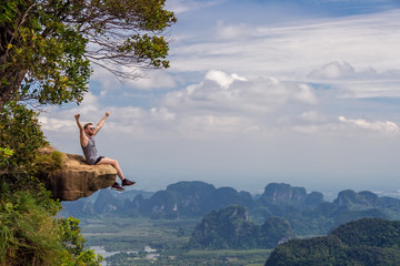 Young man tourist sits on top of a mountain