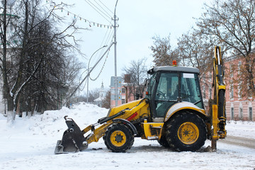 tractor for snow removal is parked on a city street