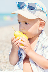 Toddler boy eating a pear in the summer