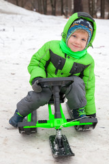 Cute boy on sleigh in snow park