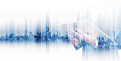Businessman working on digital tablet with double exposure city, concepts of technology business development