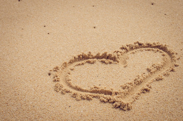 Copy space of  heart shape on sand beach. Travel concept.