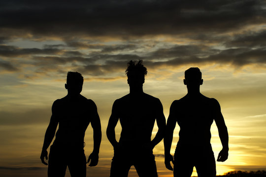 Handsome muscular men in sunset