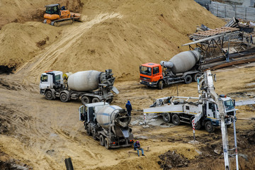 builders build a foundation from cement  to a new building ground truck mixer hard working