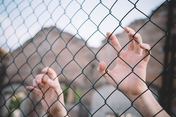 Refugee hands keeping metal fence mesh