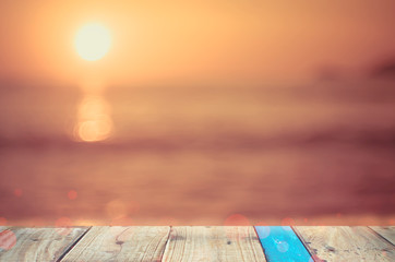 Blur tropical sunset beach with bokeh wave on old empty wood table background.