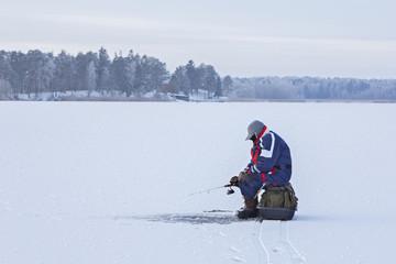 Ice fishing. Fisherman sitting on a frozen lake for fishing
