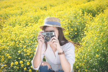 Asian hipster cute teen girl with camera in yellow flower garden