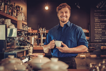 Fototapeta Handsome barista tasting a new type of coffee in his coffee shop obraz