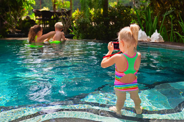 Happy family. Mother, baby swim with fun in swimming pool, relax at pool side. Girl take picture by photo camera. Healthy lifestyle, active parent, people recreation on beach summer holiday with child