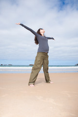 brunette brown hair pregnant woman with grey shirt green trousers and black sunglasses happy joyful open arms in sand beach ocean in Asturias Spain