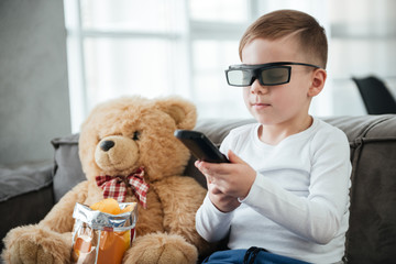 Boy wearing 3d glasses watching TV while holding remote control.