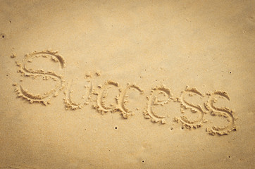 Success words hand writing on sand beach texture background.