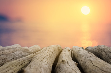 Blur beautiful tropical sunset beach with bokeh sun light wave on copy space empty old wood table abstract background.