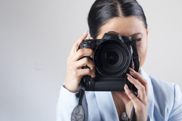 Young businesswoman holding a professional dslr camera
