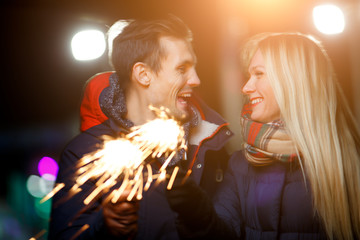 Beautiful couple with sparklers outdoors