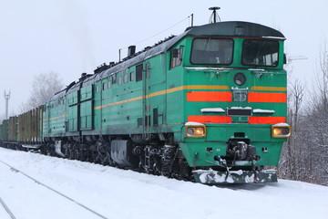 Локомотив с прицепленными вагонами стоит на заснеженном пути.