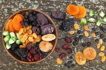 Mix of dried fruits on a dark wood background. Top view.
