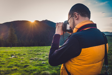 Nature photographer tourist with camera taking a photo in the mountains. Dreamy sunset landscape, spring green meadow and mountain top in the bsckground. Back view